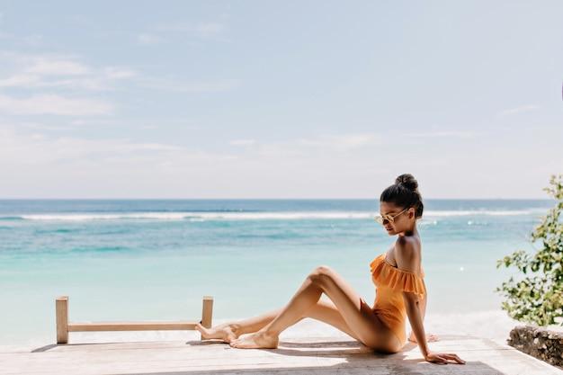 ビーチに座っているオレンジ色の服装のロマンチックな日焼けした女の子。海岸の地面にポーズをとるサングラスの魅惑的な白人女性モデル。
