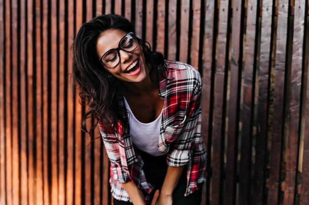 Ragazza abbronzata romantica che ride mentre posa vicino al recinto di legno. felice signora dai capelli scuri in camicia a scacchi sorridente con gli occhi chiusi.