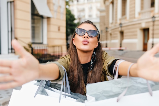 Романтичная загорелая женщина в солнцезащитных очках держит покупки и позирует с целующим выражением лица