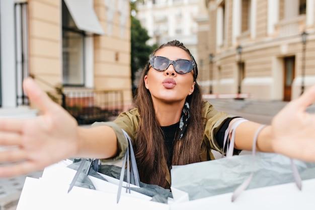Romantica donna abbronzata in occhiali da sole che tengono gli acquisti e in posa con l'espressione del viso baciante