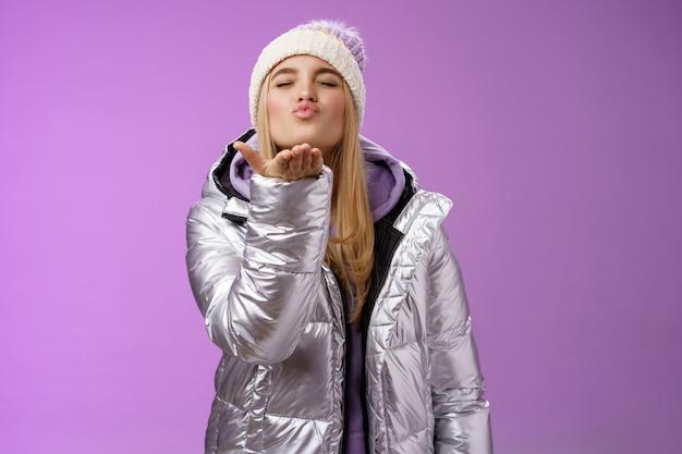 낭만적 인 부드러운 부드러운 귀여운 여자 친구 금발 머리 입고 모자 세련된 실버 재킷 닫기 눈 접는 입술 muah 입술 근처 손을 잡고 불어 공기 키스 열정적으로 사랑 동정, 보라색 배경을 느낍니다.