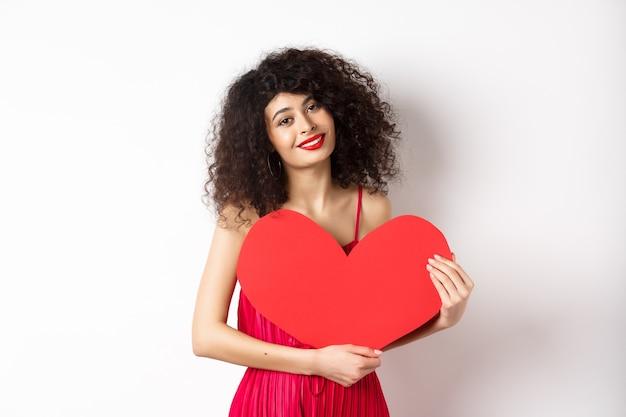 곱슬 머리를 가진 낭만적 인 부드러운 여자, 큰 붉은 마음을 포옹 하 고 웃 고, 흰색 배경에 서있는 사랑으로 봐.
