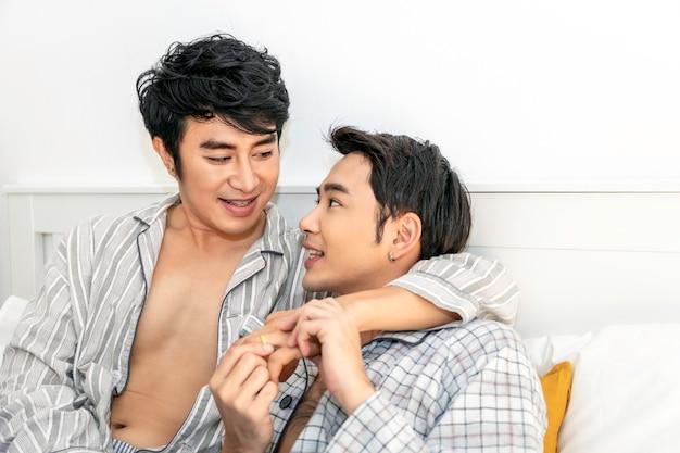 ロマンチックな時間。パジャマ姿でアジアの同性愛カップルがベッドで抱擁とキス