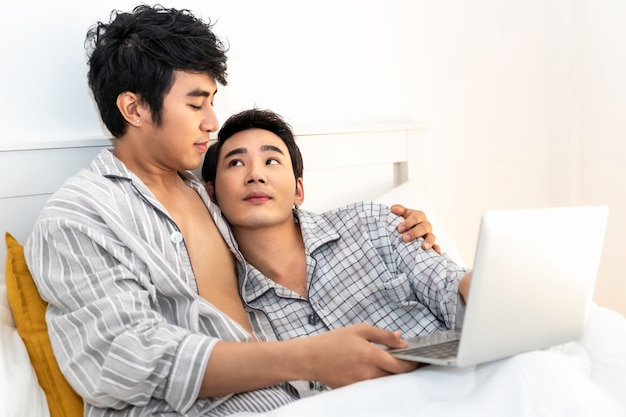 Romantic time.asian homosexual couple in pajamas shopping online with computer notebook in the bed