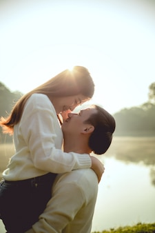 Romantic time of lovely asian couple in the lake park on morning. they are will be kissing together.