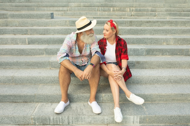 Romantic tourist couple sitting on stairs. bearded senior man and young woman.
