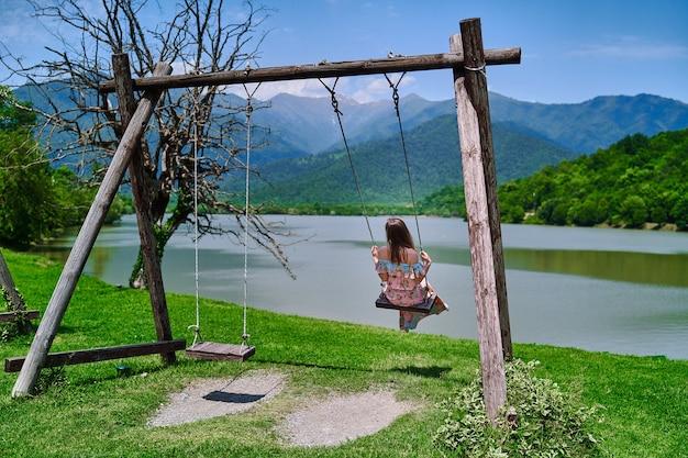 긴 드레스를 입은 낭만적인 여행자 소녀는 호수와 산의 전망을 감상하며 혼자 그네를 탄다. 아름다운 자유 순간의 삶과 자연 속에서 고요한 고요하고 평화로운 고요한 분위기를 즐기십시오. 뒷모습