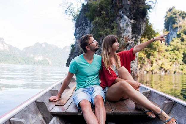 Romantic traveling couple spending vacation time together , sitting on long tail boat, exploring wild nature of khao sok national park.