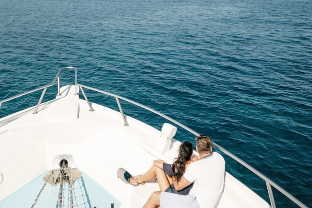 Romantic vacation and luxury travel. young loving couple sitting on the sofa on the modern yacht deck. sailing the sea side view