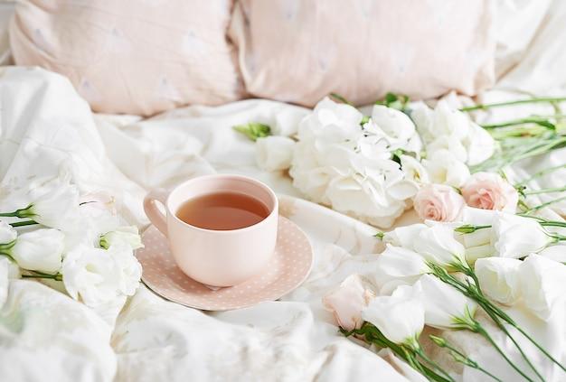 Романтический завтрак на день святого валентина в постели с чашкой чая и цветами на кровати