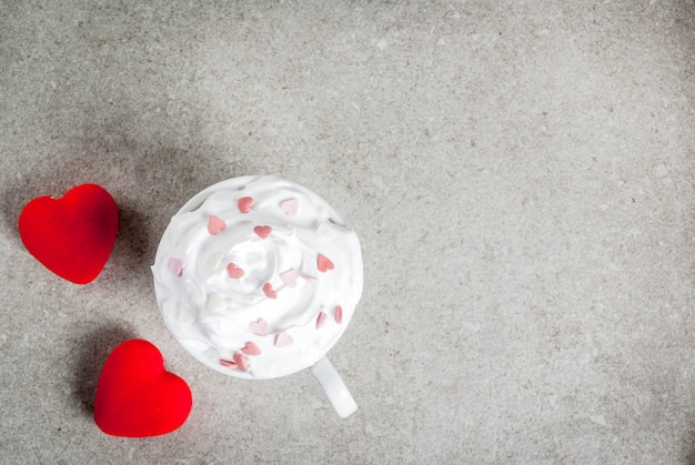 Romantic , valentine's day. cup for coffee or hot chocolate, with whipped cream and sweet hearts, with two plush red hearts,   top view