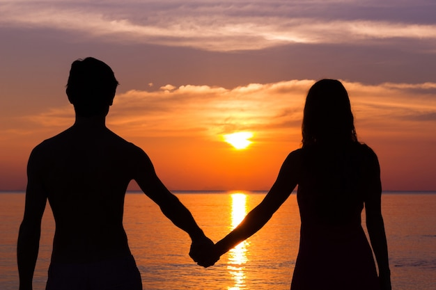 Romantic valentine's day scene of a young couple silhouettes holding hands by the sea staring at colorful sunset.