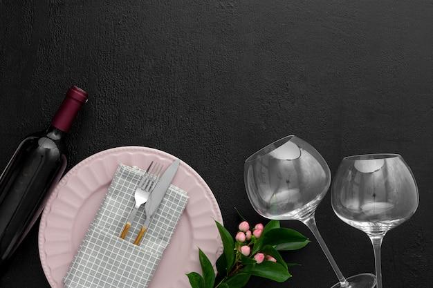 Романтическая сервировка стола на день святого валентина с вином, бокалами и красной коробкой