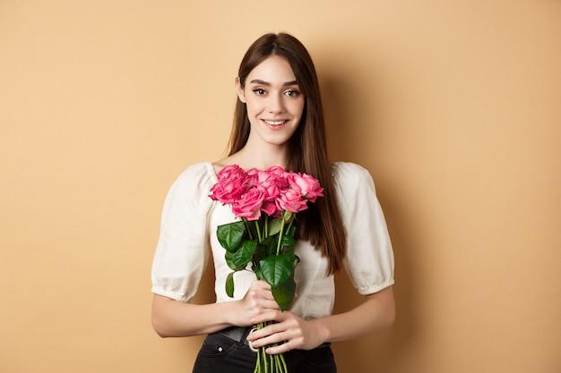 ロマンチックなバレンタインデーのコンセプトピンクのバラを保持し、幸せに立って笑顔の美しい若い女性...