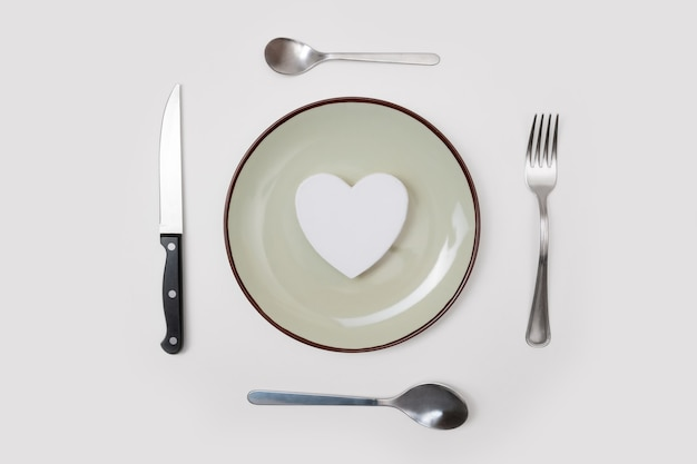 Romantic valentines day dinner idea concept. heart on plate and silver wear on white background.