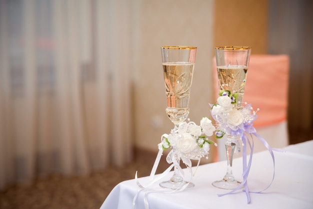 Romantic view of wedding glasses with champagne on white tablecloth in the restaurant.