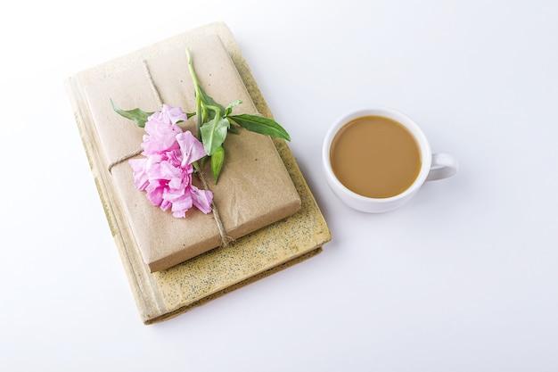 古い本、お茶やコーヒー、クラフト紙で包まれ、ピンクの花で飾られたかわいいギフトボックスとロマンチックなヴィンテージの静物