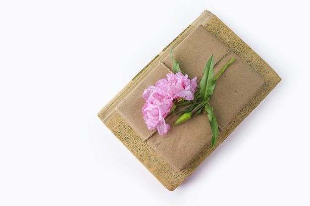 Romantic vintage still life with old book and pretty gift box wrapped with craft paper and decorated with pink flower on white background