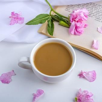 ピンクの花、古い本、春のお茶やコーヒー、庭で夏の日のロマンチックなヴィンテージの静物