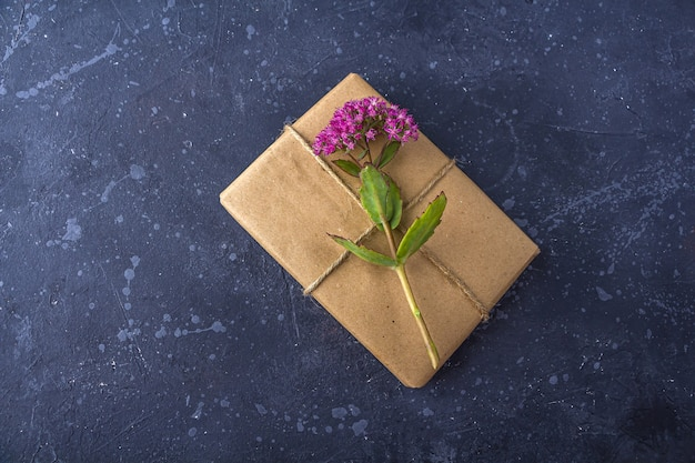 Romantic vintage still life with pretty gift box wrapped with craft paper and decorated with pink flower on dark background