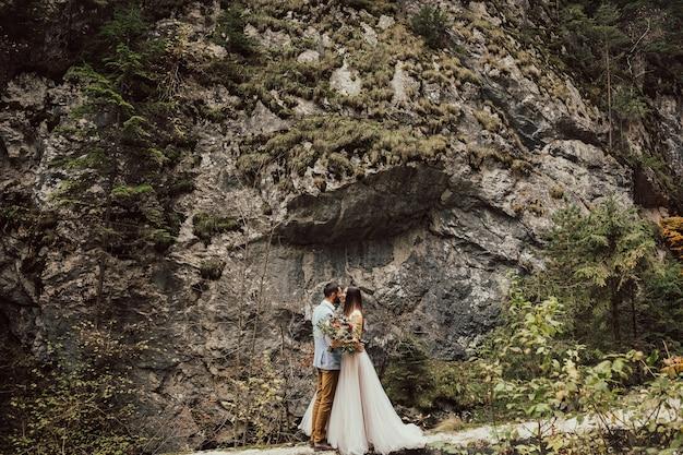 大きな岩の近くで抱き締めるロマンチックな結婚式のカップル