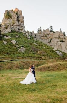 사랑에 빠진 낭만적인 웨딩 커플은 산과 숲을 산책합니다.