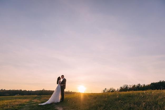素晴らしい景色と夕日の山の頂上でポーズをとってロマンチックな結婚式のカップル