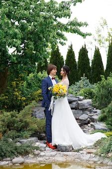 ロマンチックな結婚式の瞬間、新婚夫婦の幸せな肖像画、花嫁と花婿が公園を散歩中に抱擁