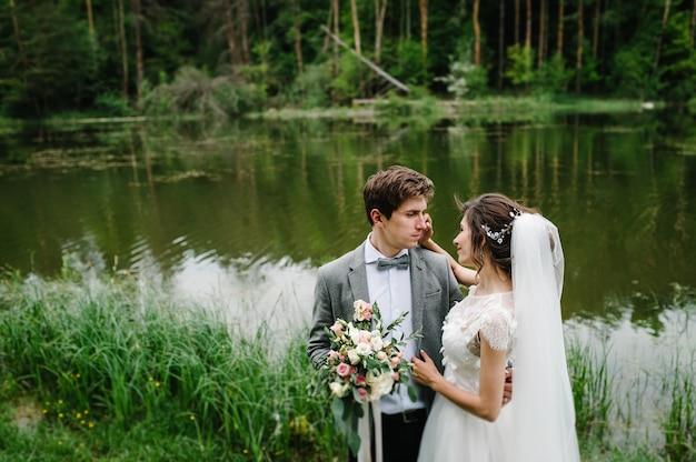 Романтический момент свадьбы, пара молодоженов смотрит и целуется