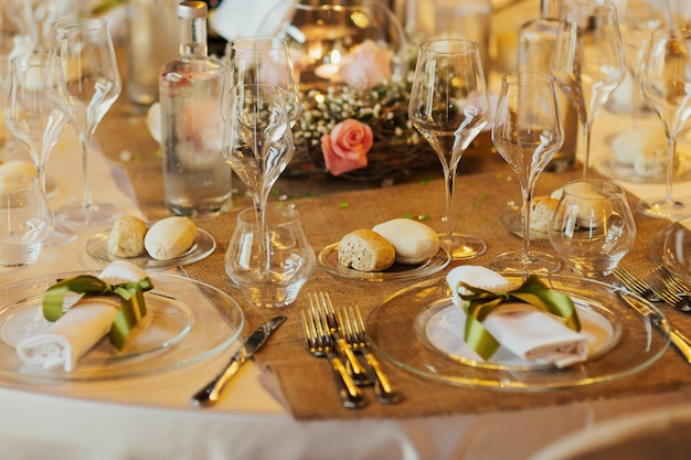 Romantic wedding table arrangement with beige tablecloth and napkins.