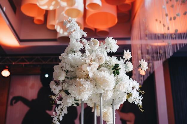 白いバラのラナンクを含む大きな緑豊かな花の花束とロマンチックな結婚式のテーブルトップのレイアウトの装飾...