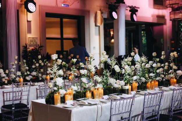 白いバラ、ラナンキュラス、ペルシャキンポウゲ、白い蘭、キャンドルなどの大きな緑豊かな花の花束とロマンチックな結婚式のテーブルトップレイアウトの装飾。高品質の写真