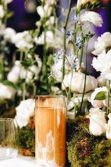 흰 장미, 라넌큘러스, 페르시아 미나리 아재비, 흰 난초 및 양초를 포함한 크고 무성한 꽃 부케로 낭만적인 웨딩 테이블 상단 레이아웃 장식. 고품질 사진