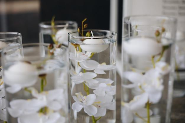 흰 장미 라넌큘러스 미나리 아재비 흰 난초와 양초를 포함한 크고 무성한 꽃 부케가 있는 낭만적인 웨딩 테이블 상단 레이아웃 장식
