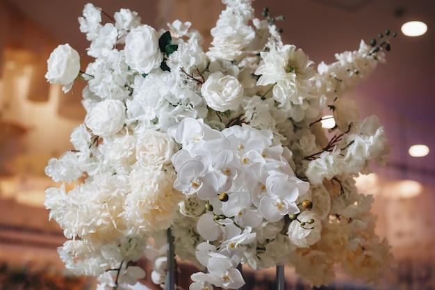 白いバララナンキュラスペルシャキンポウゲ白い蘭とキャンドルを含む大きな緑豊かな花の花束とロマンチックな結婚式のテーブルトップレイアウトの装飾