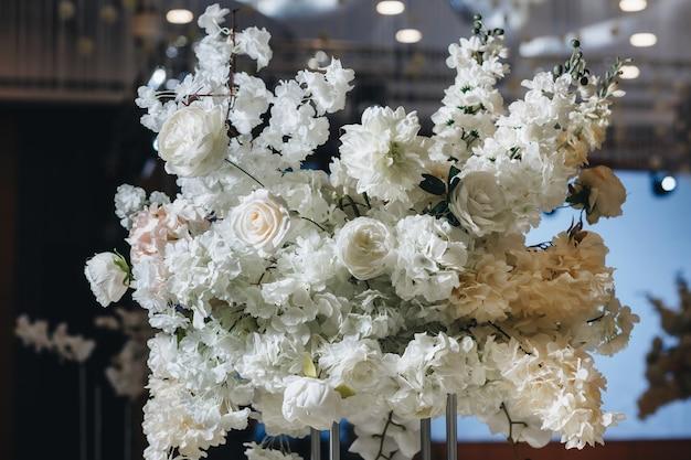 Романтический свадебный декор столешницы с большими пышными цветочными букетами, включая белые розы, лютики, персидские лютики, белые орхидеи и свечи