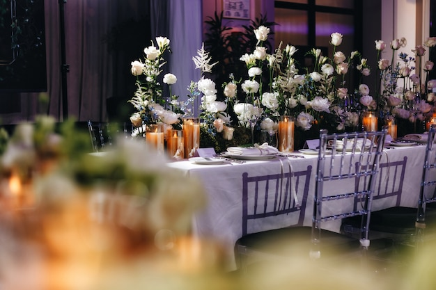 Romantic wedding table top layout decor with large lush floral bouquets including white roses, ranunculus, persian buttercups, white orchids and candles. high quality photo