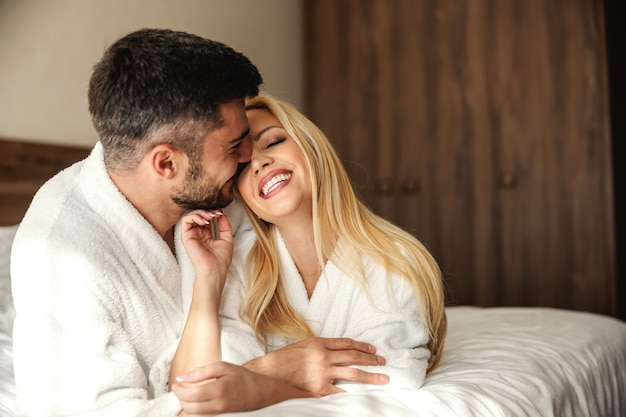 ロマンチックな週末の結婚記念日。ホテルの部屋で優しいタッチとキスで目を覚ます。高級スパホテルの美しいカップルは、ポジティブなエネルギーに満ちています。キス、愛、カップルの前の瞬間