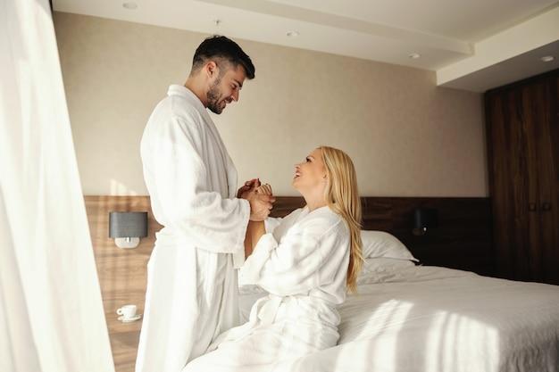 子供がいないロマンチックな週末ホテルの部屋で優しいタッチとキスで目を覚ます高級スパホテルの美しいカップルは、ストレスの多い1週間の後にポジティブなエネルギーで満たされますバスローブでの快適さ