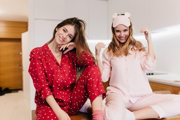 ロマンチックな白人の女の子は、ピンクのナイトスーツと幸せを表現するアイマスクを身に着けています。笑顔でかなり茶色の髪の女性の屋内ショット。