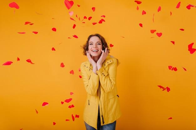 Romantica ragazza bianca con l'espressione del viso carino in posa con cuori rossi. foto dell'interno della giovane donna riccia che celebra il giorno di san valentino con il sorriso.