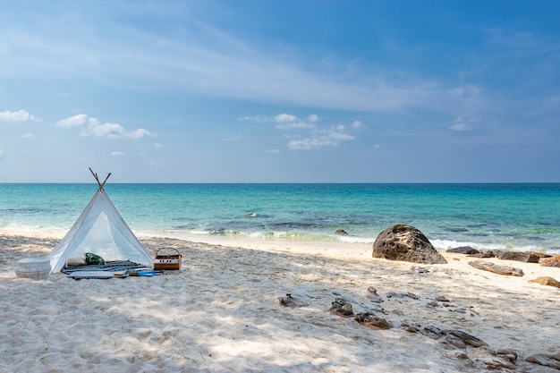 Romantic white picnic tent on white sand beach with crystal clear water and blue sky