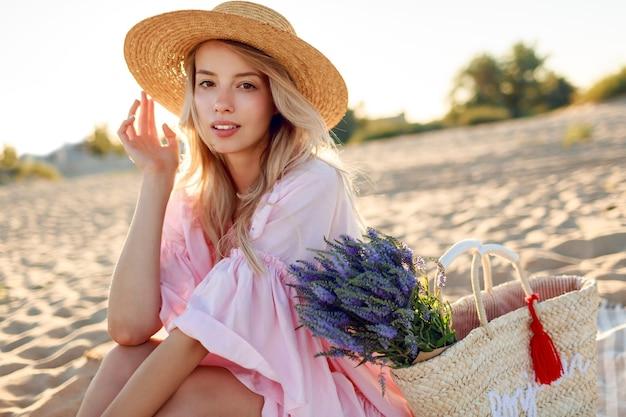 トレンディな帽子とビーチでポーズをとるエレガントなピンクのドレスのロマンチックな白人女性。ストローバッグと花の花束を保持しています。