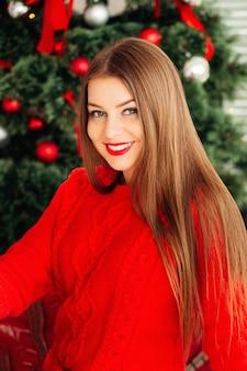 Романтичная зимняя хипстерская девушка в вязаном красном свитере возле елки