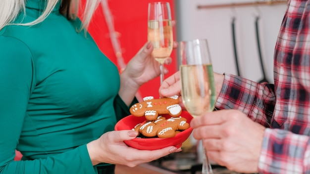 Romantic winter holidays celebration. cropped shot of couple drinking champagne with gingerbread cookies.