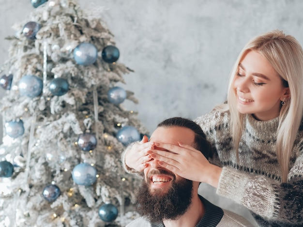 낭만적 인 겨울 휴가. 그녀의 남자 친구의 눈을 가리고 선물로 그를 놀라게하는 레이디