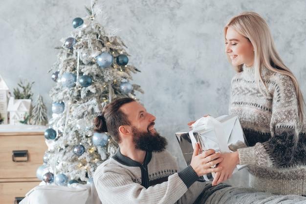 낭만적 인 겨울 휴가. 그녀의 남자 친구에게 선물을주는 아가씨. 집에서 크리스마스를 축하하는 행복 한 커플입니다.