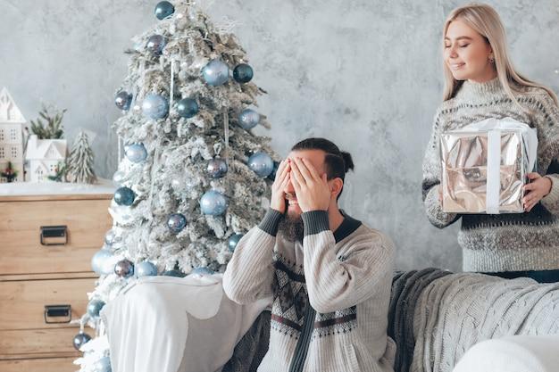 낭만적 인 겨울 휴가. 레이디는 남자 친구에게 깜짝 선물을 준비했습니다. 남자는 선물에 대해 흥분하고 눈을 가리고 웃고 있습니다.