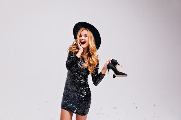 Romantic woman in black dress holding her shoes in hand. indoor photo of well-dressed blonde girl posing in hat.