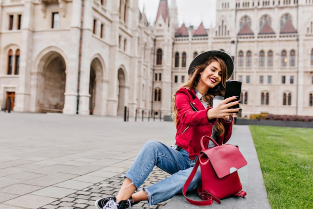 Romantic woman in casual clothes making selfie with cup of tea